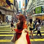 Main dans la main, elle conduit son copain à travers le monde