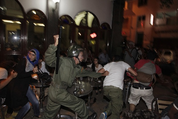 A riot policeman charges at protesters during a demonstration against a royal pardon for a Spanish paedophile, in Rabat