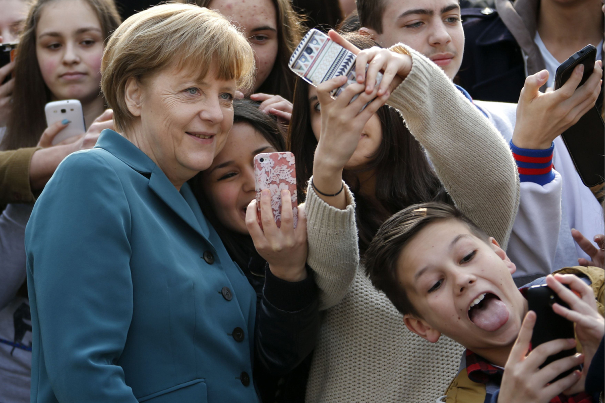 Students take mobile phone 'selfies' with German Chancellor Angela Merkel as she arrives for visit at Robert-Jungk Europe high school in Berlin
