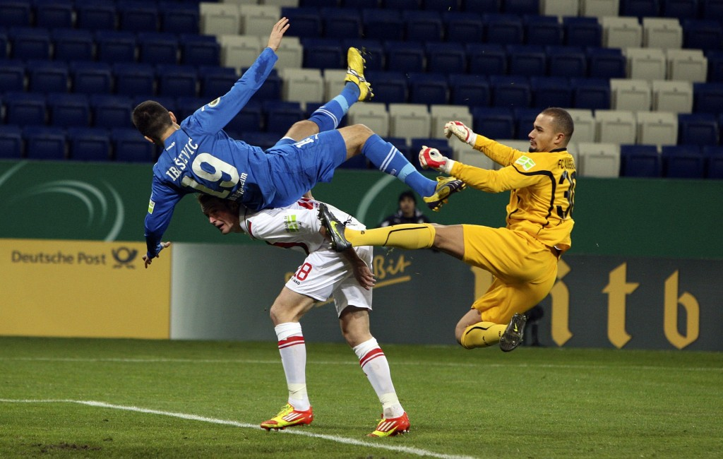 Hoffenheim's Ibisevic challenges Augsburg's Amsif and Callsen-Bracker during their German soccer cup match in Sinsheim