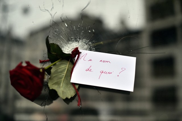 (FILES) This file photo taken on November 14, 2015 shows A rose with a sign reading 'In the name of what?' in a bullet hole in the window of a Japanese restaurant next to the cafe 'La Belle Equipe', Rue de Charonne, in Paris following a series of coordinated attacks in and around Paris late on November 13. At least 128 people were killed in the Paris attacks on the evening of November 13, with 180 people injured, 80 of them seriously, police sources told AFP. / AFP / LOIC VENANCE