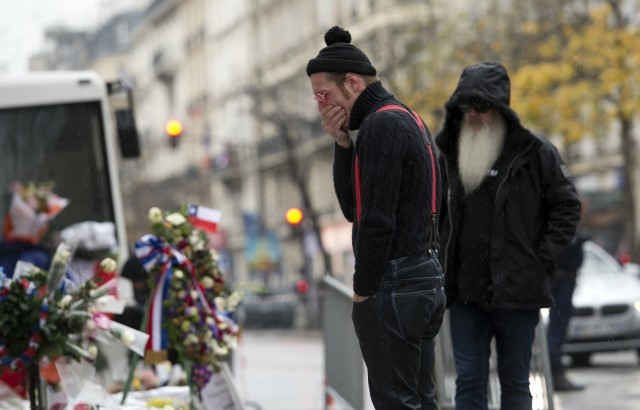 Singer of the US rock group Eagles of Death metal Jesse Hughes (L) and guitarist Dave Catching pay tribute to the victims of the November 13 Paris terrorist attacks at a makeshift memorial in front of the Bataclan concert hall on December 8, 2015 in Paris. The Eagles of Death Metal band returned to the Bataclan concert hall in Paris, nearly a month after they survived a jihadist attack there in which 90 people died. / AFP / MIGUEL MEDINA