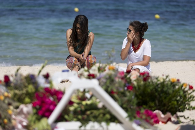 Tourists mourn at the site of a shooting attack on the beach in front of the Riu Imperial Marhaba Hotel in Port el Kantaoui, on the outskirts of Sousse south of the capital Tunis, on June 28, 2015. The Islamic State (IS) group claimed responsibility on June 27 for the massacre in the seaside resort that killed nearly 40 people, most of them British tourists, in the worst attack in the country's recent history. AFP PHOTO / KENZO TRIBOUILLARD / AFP / KENZO TRIBOUILLARD