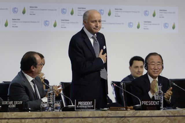 French Foreign Minister Laurent Fabius (C) is applauded by French President Francois Hollande (L) and United Nations Secretary General Ban Ki-moon (R) after a statement at the COP21 Climate Conference in Le Bourget, north of Paris, on December 12, 2015. The years-long quest for a universal pact to avert catastrophic climate change neared the finish line today with conference host France announcing that the final draft had been completed in the early hours of the morning. AFP PHOTO / MIGUEL MEDINA / AFP / MIGUEL MEDINA