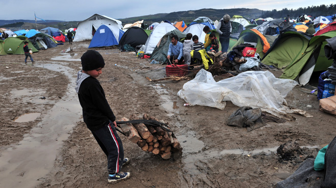 A boy carries wood on March 10, 2016 at the Greek-Macedonian border near the Greek village of Idomeni where thousands of refugees and migrants are trapped by the Balkan border blockade. The German and Greek leaders blasted Balkan countries for shutting their borders to migrants ahead of an EU ministers meeting on March 10. Greek authorities said there were 41,973 asylum seekers in the country, including some 12,000 stuck at Idomeni on the closed Macedonian border. / AFP / SAKIS MITROLIDIS
