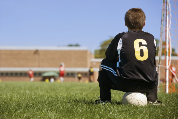 young boy watching soccer game from behind goal on sidelines.