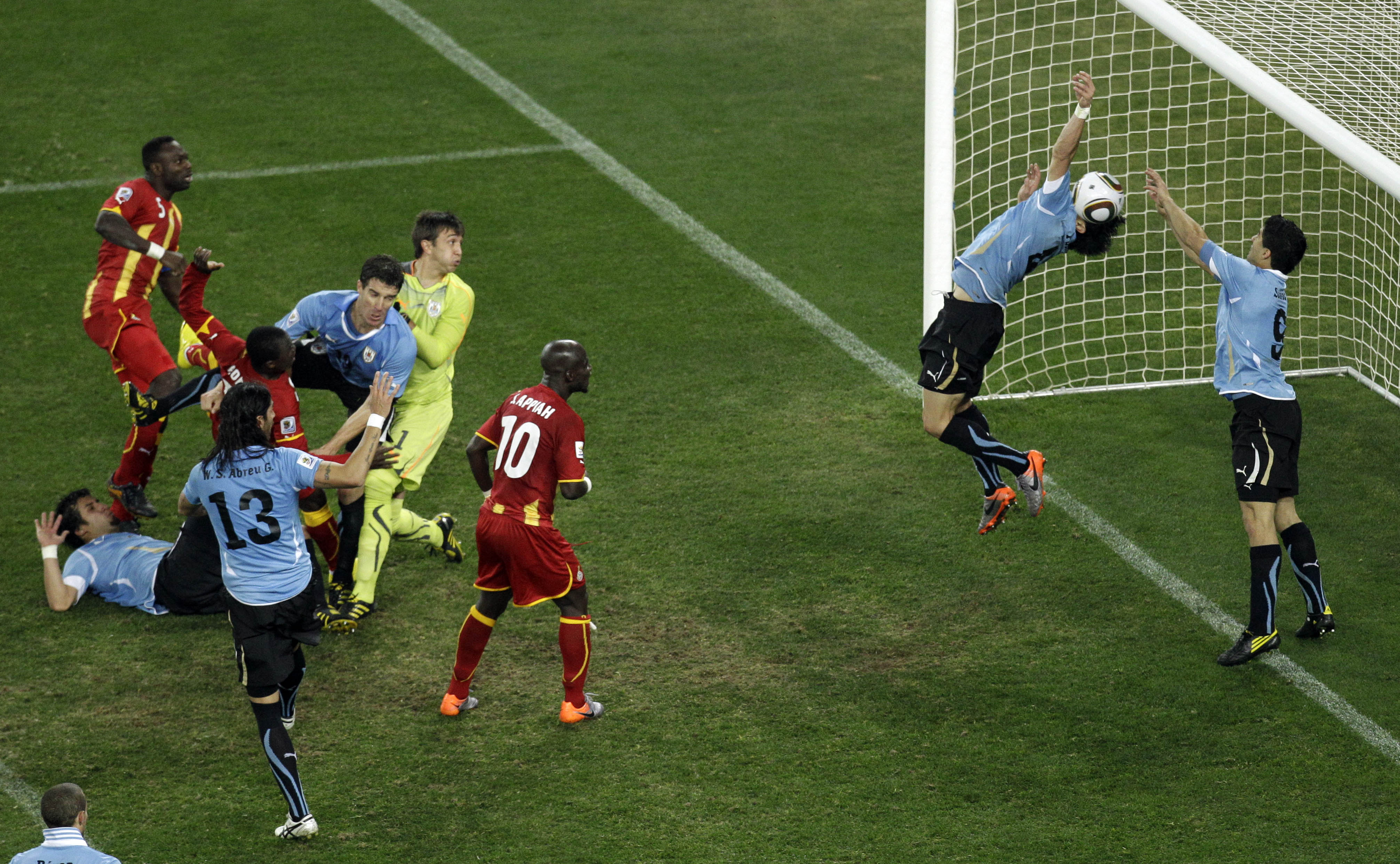 Uruguay's Luis Suarez, right, reaches his hands to the ball to give away a penalty during the World Cup quarterfinal soccer match between Uruguay and Ghana at Soccer City in Johannesburg, South Africa, Friday, July 2, 2010. (AP Photo/Themba Hadebe)