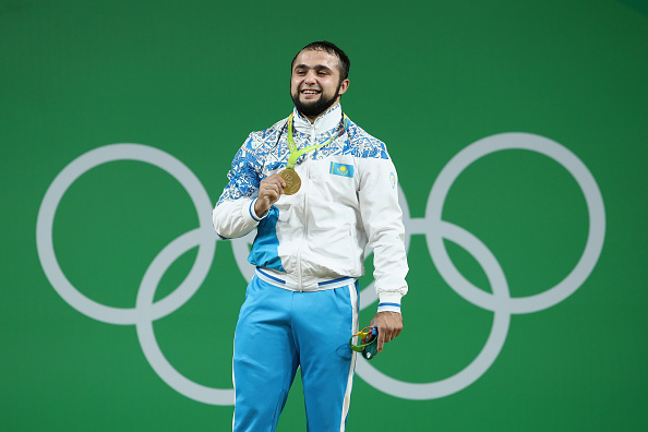 RIO DE JANEIRO, BRAZIL - AUGUST 10: Gold medalist, Nijat Rahimov of Kazakhstan celebrates on the podium after the Men's 77kg Group A weightlifting contest on Day 5 of the Rio 2016 Olympic Games at Riocentro - Pavilion 2 on August 10, 2016 in Rio de Janeiro, Brazil. (Photo by Julian Finney/Getty Images)
