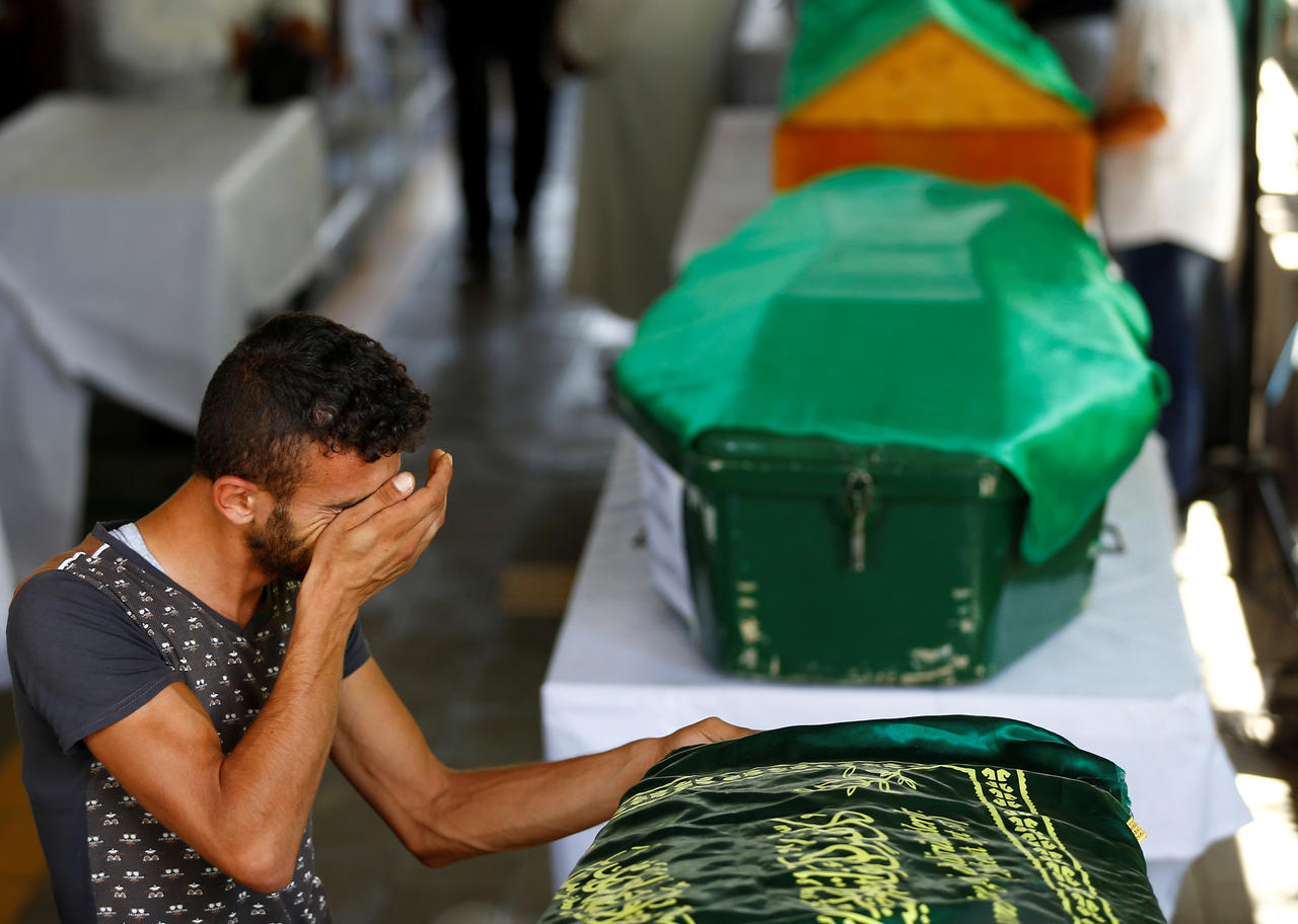 A family member of a victim of a suicide bombing at a wedding celebration mourn over his coffin during a funeral ceremony in the southern Turkish city of Gaziantep, Turkey, August 21, 2016. REUTERS/Osman Orsal - RTX2MEMK